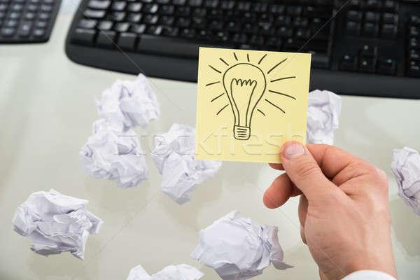 Businessman Holding Lit Bulb Drawn On Sticky Note Stock photo © AndreyPopov