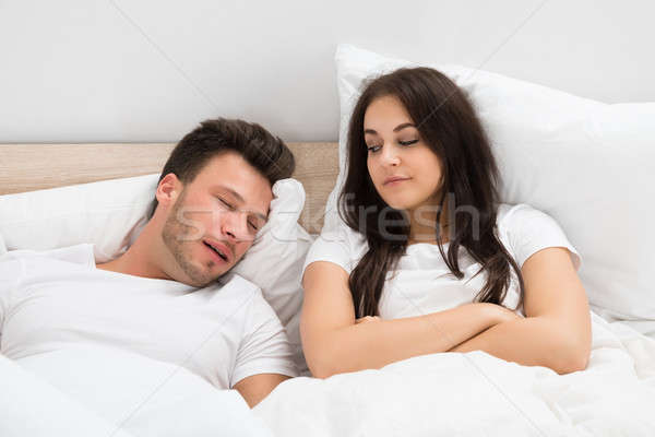Woman Looking At Man Snoring In Bed At Home Stock photo © AndreyPopov