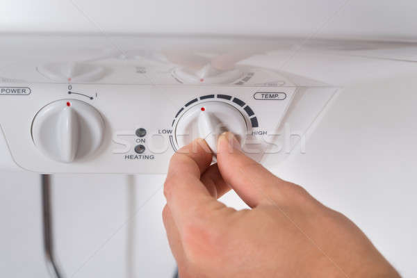 Person Turning The Knob Of Electric Boiler Stock photo © AndreyPopov