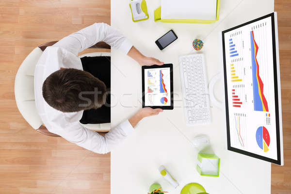 Businessman Analyzing Graph On Computer At Desk Stock photo © AndreyPopov