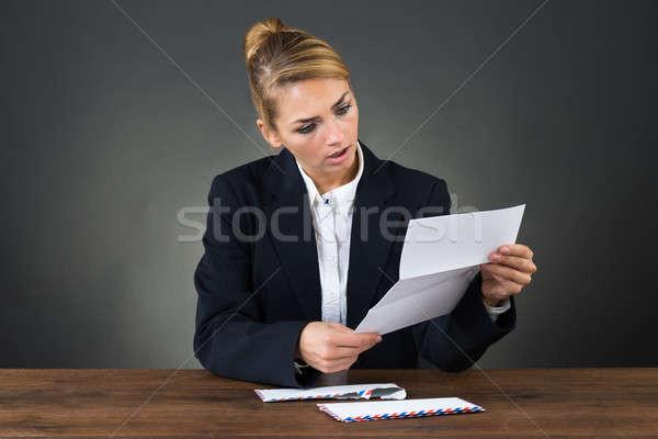 Shocked Businesswoman Reading Letter At Desk Stock photo © AndreyPopov