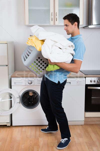 Człowiek ciężki kosz na bieliznę młody człowiek pralka Zdjęcia stock © AndreyPopov