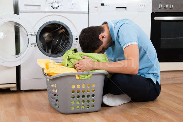 Exhausted Man With Laundry Basket Sitting By Washing Machine Stock photo © AndreyPopov