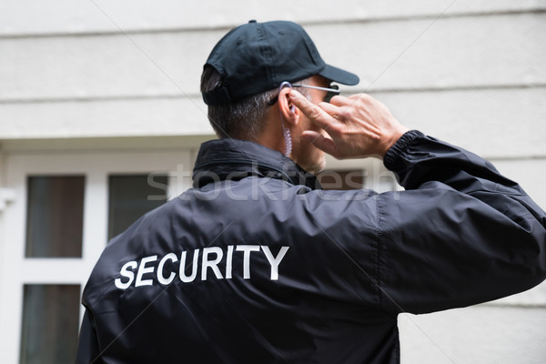 Security Guard Listening To Earpiece Against Building Stock photo © AndreyPopov