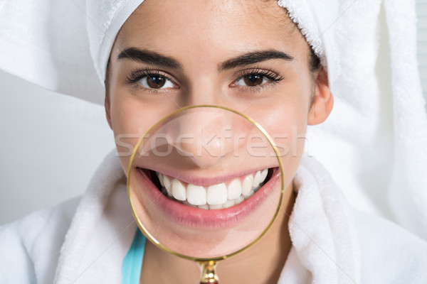 Happy Woman Showing White Teeth Through Magnifying Glass Stock photo © AndreyPopov
