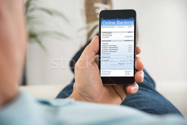 Close-up Of Person With Mobile Phone Doing Online Banking Stock photo © AndreyPopov