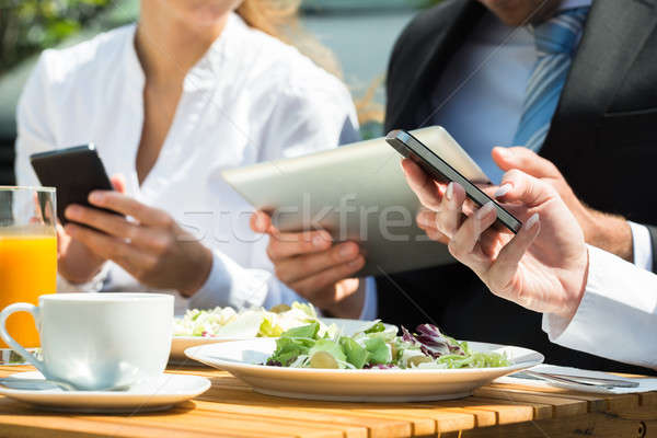 Close-up Of Businesspeople Using Digital Tablet And Mobile Phone Stock photo © AndreyPopov