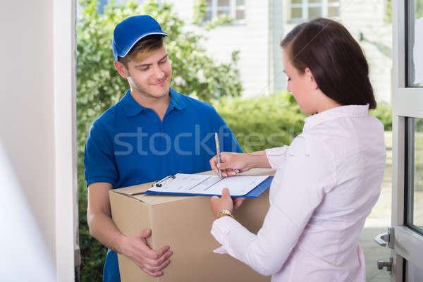 Vrouw ondertekening ontvangst levering pakket Stockfoto © AndreyPopov