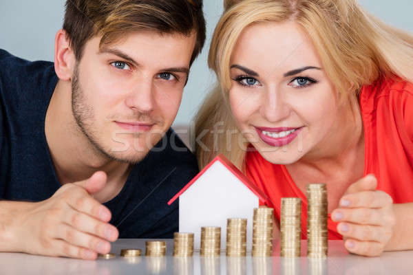 Couple Protecting House Model With Stacked Coins Stock photo © AndreyPopov