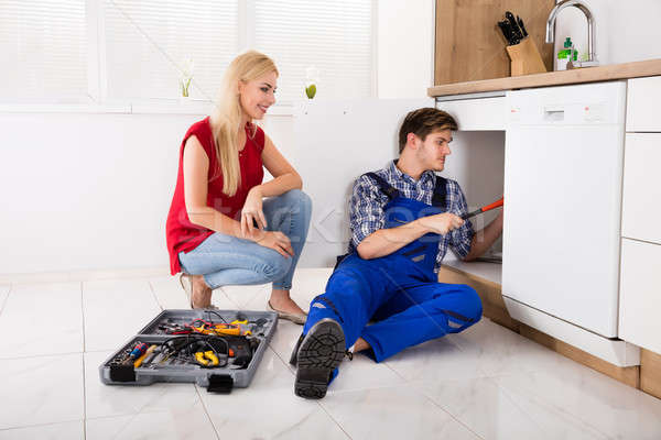 Woman Looking At Male Plumber Fixing Kitchen Sink Stock photo © AndreyPopov