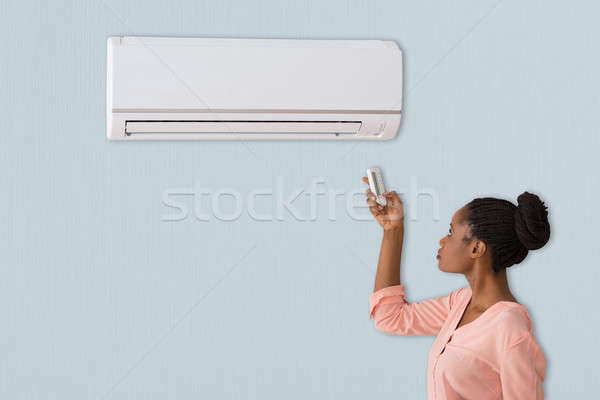 Woman Using Air Conditioner Stock photo © AndreyPopov