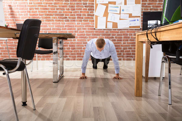 Stock photo: Businessman Doing Push Up In Office