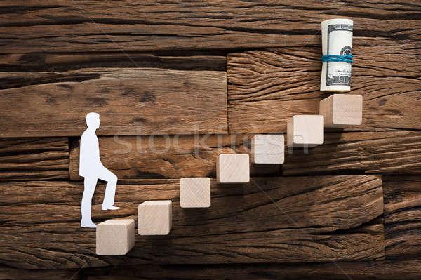 Paper Businessman Climbing Ladder Leading Towards Money Stock photo © AndreyPopov