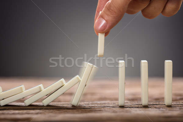 Businessman Picking Domino Piece On Wooden Table Stock photo © AndreyPopov