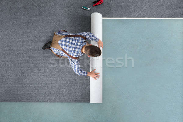 Young Male Worker In Overalls Rolling Carpet Stock photo © AndreyPopov