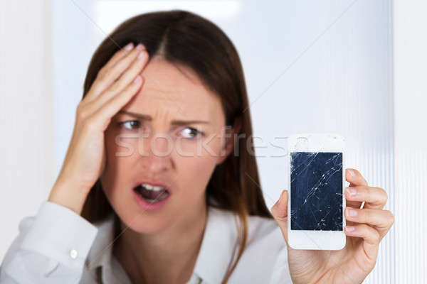 Worried Woman Holding Smartphone With Cracked Screen Stock photo © AndreyPopov