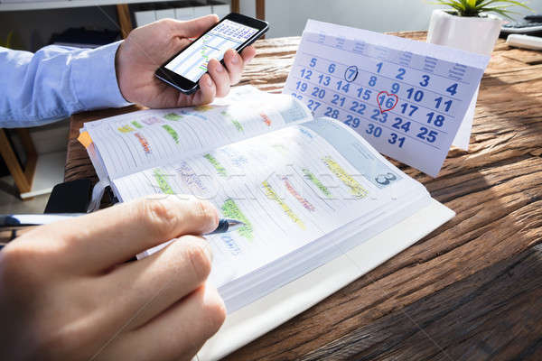 Businessperson's Hand Planning Schedule In Diary Stock photo © AndreyPopov