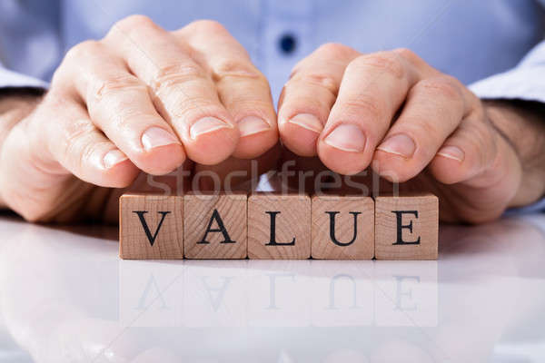 Human Hand Over Wooden Block With Value Text Stock photo © AndreyPopov