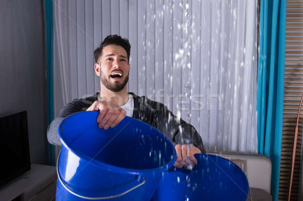 Man Holding Bucket While Water Leakage Stock photo © AndreyPopov