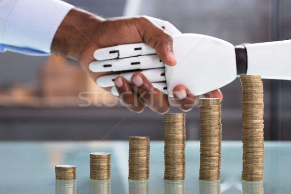 Man Shaking Hand With Robot With Coin Stack Stock photo © AndreyPopov