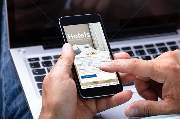 Man Booking Hotel Using Smartphone Stock photo © AndreyPopov