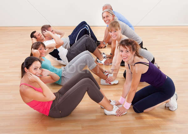 Happy people working out in a gym Stock photo © AndreyPopov