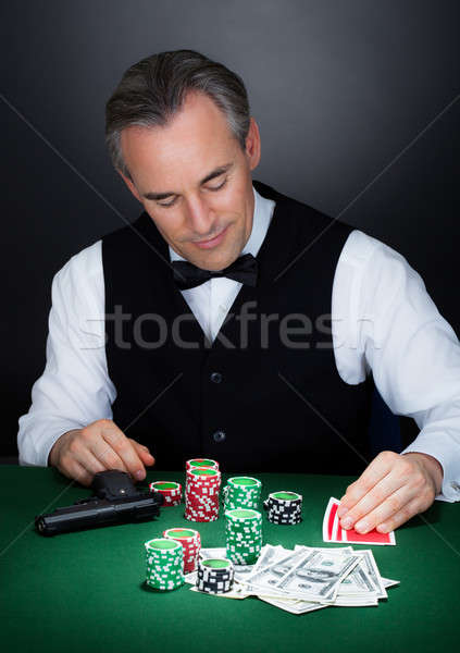 Stock photo: Portrait of a croupier looking at playing cards