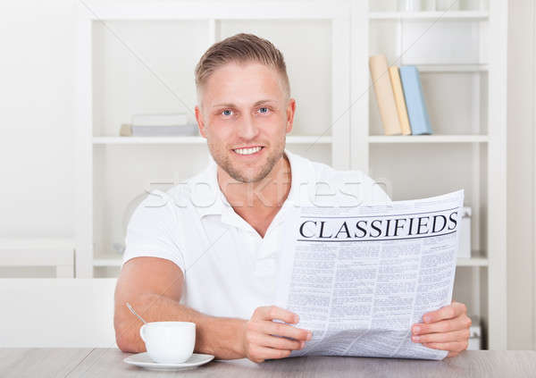 Excited man reading the classifieds Stock photo © AndreyPopov