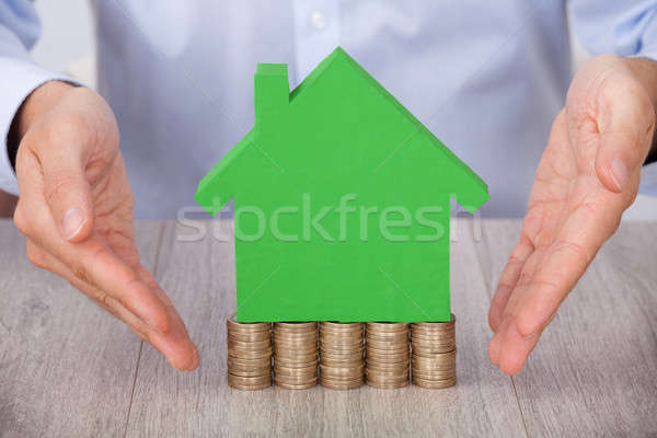 Businessman Presenting Green Model House On Stacked Coins Stock photo © AndreyPopov