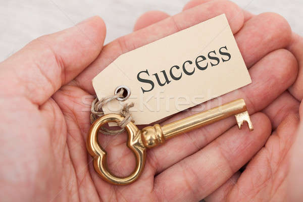 Stock photo: Man Holding Key With Success Tag