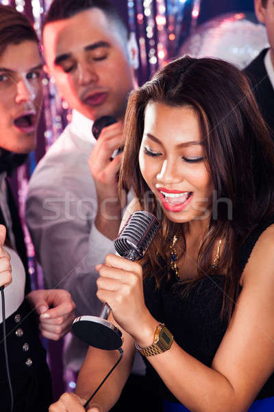 Woman Singing Into Microphone At Karaoke Party Stock photo © AndreyPopov