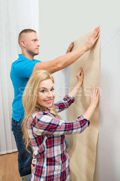 Young Couple Holding Wallpaper On Wall Stock photo © AndreyPopov