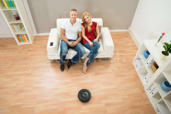 Couple On Sofa With Robotic Vacuum Cleaner On Floor Stock photo © AndreyPopov