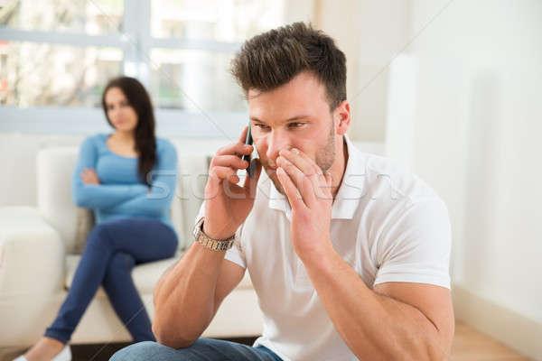Uomo parlando telefono cellulare moglie curiosità guardando Foto d'archivio © AndreyPopov