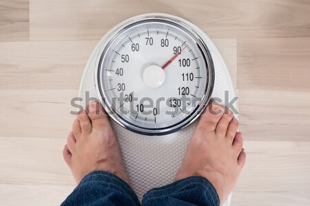 Man Standing On Weighing Scale Stock photo © AndreyPopov