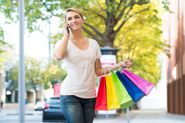 Woman Using Mobile Phone While Carrying Shopping Bags Stock photo © AndreyPopov
