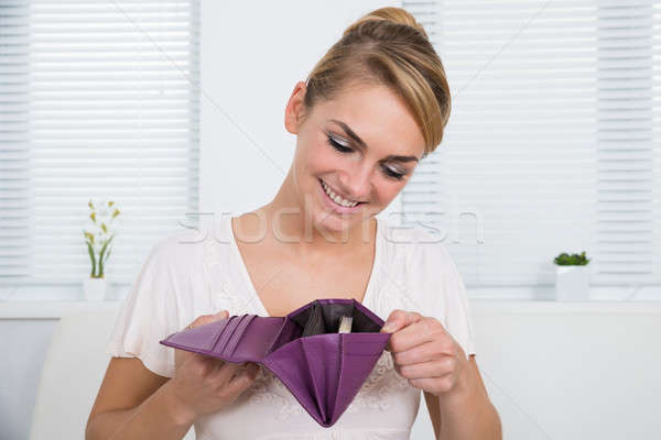Woman Looking At Money In Purse Stock photo © AndreyPopov
