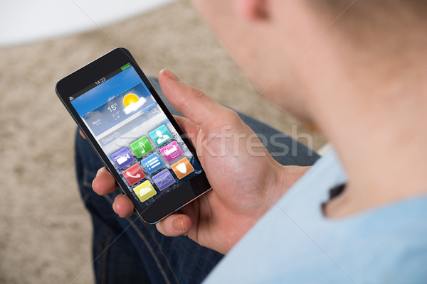 Man Holding Smartphone With Colorful Application Icons Stock photo © AndreyPopov