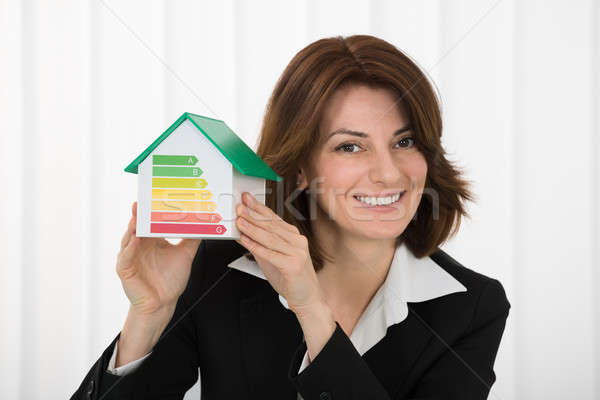 Businesswoman Holding House Model With Energy Efficiency Rate Stock photo © AndreyPopov