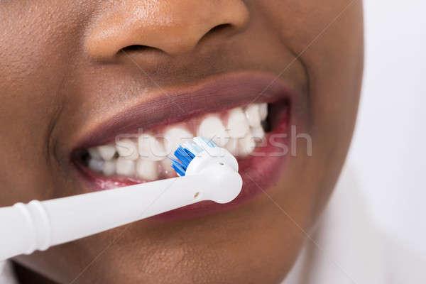 Mujer eléctrica cepillo de dientes primer plano casa Foto stock © AndreyPopov