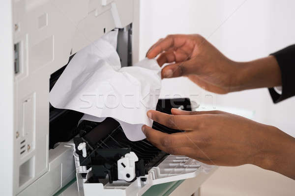 Businesswoman Hand Removing Paper Stucked In Printer Stock photo © AndreyPopov