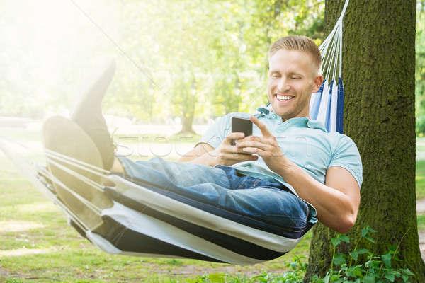 Férfi függőágy mobiltelefon fiatal boldog megnyugtató Stock fotó © AndreyPopov