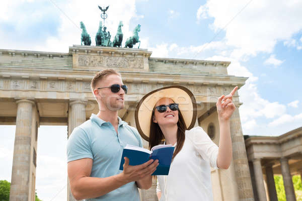 Stock photo: Young Couple Reading Tourist Guide