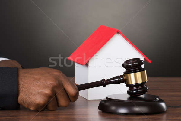 Judge Hands Hitting Gavel With House Model Stock photo © AndreyPopov
