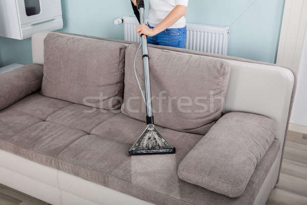 Woman Cleaning Sofa With Vacuum Cleaner Stock photo © AndreyPopov