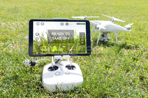 Closeup of controller and quadrocopter on grassy field at park Stock photo © AndreyPopov
