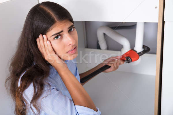 Woman Holding Head While Tightening Sink Pipe Stock photo © AndreyPopov