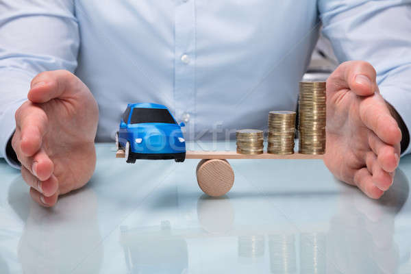Businessperson Protecting Balance Between Car And Stacked Coins Stock photo © AndreyPopov
