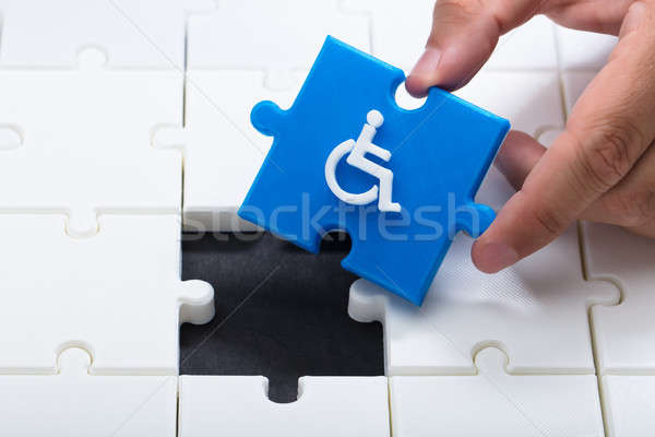 Human hand solving jigsaw puzzle with blue piece Stock photo © AndreyPopov