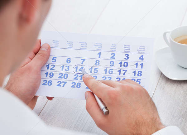 Man Marking With Pen And Looking At Date On Calendar Stock photo © AndreyPopov